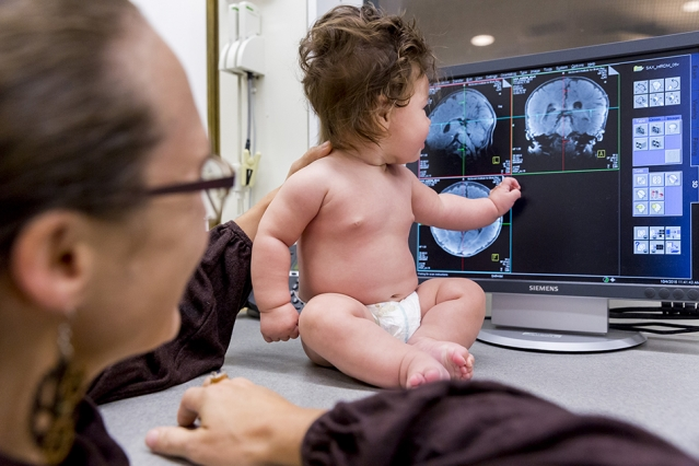 Neuroscientists at MIT have adapted their MRI scanner to make it easier to scan infants' brains as the babies watch movies featuring different types of visual input. With the new technique, the team found that in some ways, the organization of infants' brains is surprisingly similar to that of adults. Specifically, brain regions that respond to faces in adults do the same in babies, as do regions that respond to scenes. Photo: Caitlin Cunningham